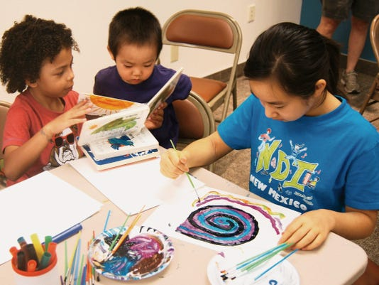 Seven-year-old Keaunu Wilson, left, shares a book with Taishi Sato, 3, while Azusa Sato, 11, works on her art during Wednesday's Make It! Open Art day at the Silver City Public Library. Randal Seyler - Sun-News