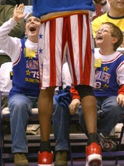Having the best seats in the house allows Drew Adair, 9, of Evansville, left, and Luke Suter, 8, of Rockport, Ind., a chance to cut-up with Kris Bruton, one of the world famous Harlem Globetrotters, at Roberts Stadium during a past performance. The two weren't sure how they happened upon the seats, but Suter thinks his dad entered him in a drawing and his name was pulled.