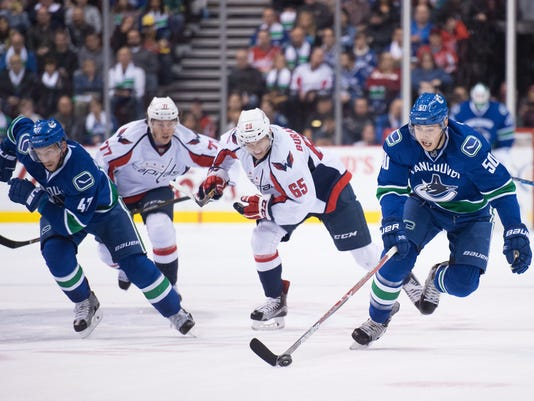 Vancouver Canucks' Brendan Gaunce, right, skates with the puck while joined by teammate Sven Baertschi, left, as Washington Capitals' Andre Burakovsky (65), of Austria, and T.J. Oshie (77) trail the play during the first period of an NHL hockey game Saturday, Oct. 29, 2016, in Vancouver, British Columbia. (Darryl Dyck/The Canadian Press via AP)