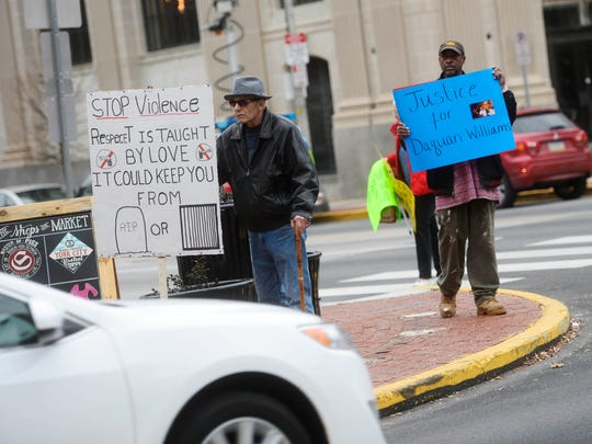 Robin Price, left, and Jakie Williams, both of York, hold signs on Continental Square. This marked the fourth time in recent months that people have met to rally against violence.