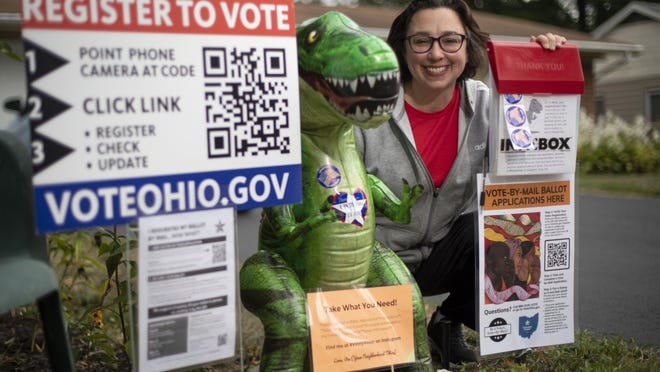Tiffany Rumbalski sits beside the voting materials, including absentee ballot requests, that she's providing outside her home in Hilliard. Her  inflatable tyrannosaurus rex, Vinny Voter, helps draw attention to the display and encourage passers-by to take the free materials and get a selfie.