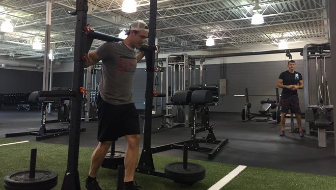 Coach Kyle Geiger demonstrates how yoke equipment is used during a workout at Lift Athletics