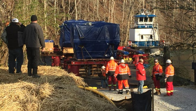 Magna and transport company employees prepare to unload a huge metal press from a barge on the Clinch River on Monday morning.