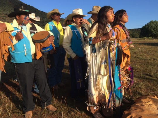 The Burnett Singers chant and beat drums, setting the rhythm for Kaila (front left) and her ceremonial partner, Malea.