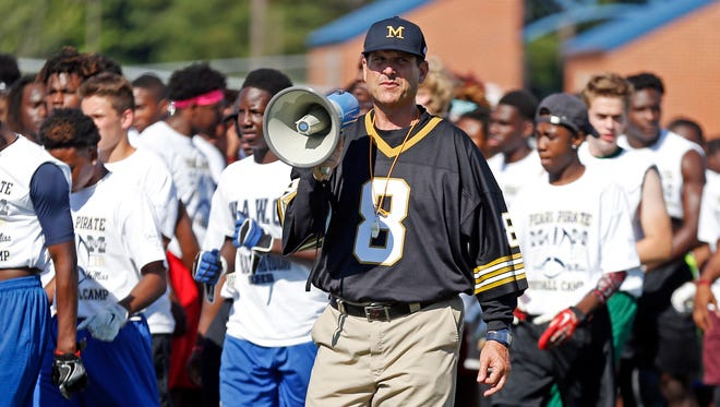 Michigan football coach Jim Harbaugh urges more than 500 high school football players to listen to his explanation of a speed drill at a satellite camp June 8, 2016, in Pearl, Miss.