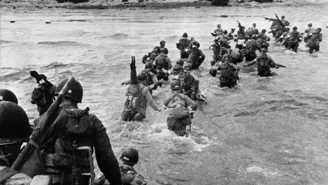 UTAH BEACH, FRANCE:  U.S. troops disembark from landing crafts during D-Day June 6, 1944, after Allied forces stormed the Normandy beaches. One month later, Henry Simmons, a Caddo Parish native, died near Utah Beach. An organization is looking for help from the community to identify Simmons' remains.
