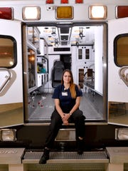 Lansing Community College paramedic program student Sierra Medrano, here in an ambulance used for training at the school, recently put her training to good use by performing CPR on a car accident victim.