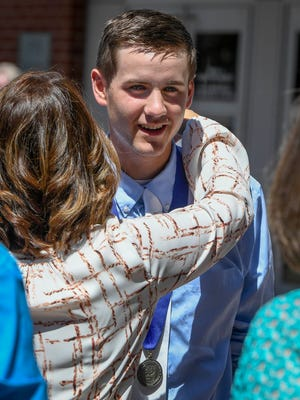 Memorial graduate Isaac Marx gets a hug from his aunt, Shelley Bontrager, as he meets with family members in front of the Old National Events Plaza following the school's commencement ceremony Sunday, May 21, 2017.