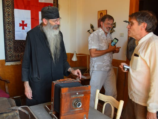 Roger L. Easton Jr being shown old camera by Father Justin at library of St. Catherine's Monastery in Egypt
