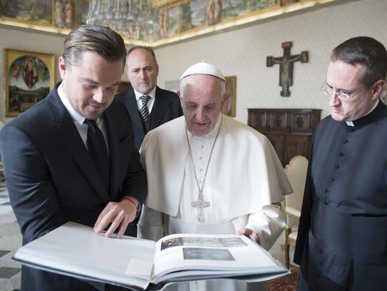 Leonardo DiCaprio shows book of art he gave Pope Francis