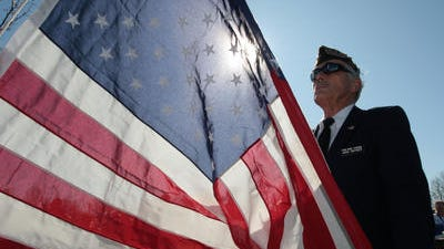 Green Township VFW Post 10380 member Jack Snyder, a U.S. Navy veteran who served in World War II, held the American flag as it was raised at one of the post's past ceremonies.