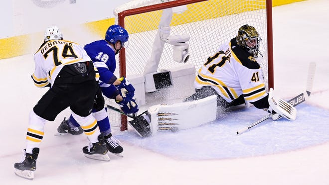 Boston Bruins goaltender Jaroslav Halak (41) stretches to make a save against Tampa Bay Lightning left wing Ondrej Palat (18) as Bruins left wing Jake DeBrusk (74) defends during first-period NHL Stanley Cup Eastern Conference playoff hockey game action in Toronto, Monday, Aug. 31, 2020.