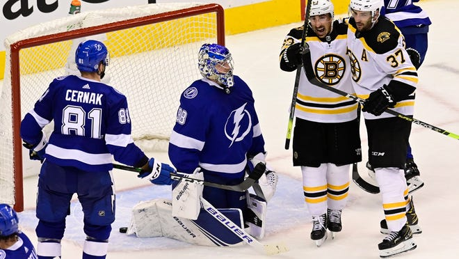 Boston Bruins left wing Brad Marchand (63) celebrates with center Patrice Bergeron (37) after scoring on Tampa Bay Lightning goaltender Andrei Vasilevskiy (88) as Lightning defenseman Erik Cernak (81) watches during the second period of Game 2 of an NHL hockey second-round playoff series, Tuesday, Aug. 25, 2020, in Toronto.
