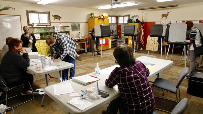 Voters fill out their ballots on Tuesday at the Boone County Conservation District polling place in Belvidere.