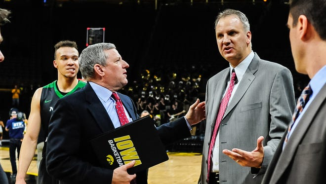 North Dakota coach Brian Jones, right, and Iowa assistant Kirk Speraw ) talk after the game at Carver-Hawkeye Arena.