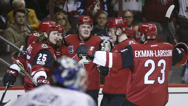 Coyotes' Lawson Crouse (67) celebrates with Jordan Martinook (48), Ryan White (25), Michael Stone (26) and Oliver Ekman-Larsson (23) after Crouse scored against the Canucks' Ryan Miller (30) in the second period at Gila River Arena on January 26, 2017 in Glendale, Ariz.