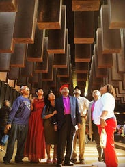 Members of the Higginbottom family (from left -- Tyrone Higginbottom, Terri Lipford, Regina Moore, EW Higginbottom, Sam Harris, Shirley Lipford, and Delois Wright -- attended the dedication of the National Memorial for Peace and Justice in Montgomery, Ala., April 26.  The pillar above their heads includes the name and lynching date of ancestor Elwood Higginbotham.