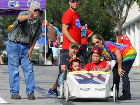 In this 2017 file photo, Charles Hosch, left, gives instructions to the driver of a Super Kids car Saturday during the ninth annual Soap Box Races in Wichita Falls. Hosch, the 1963 champion of the race, made the two-seat racers when the event returned to the city nine years ago so that special needs children can also experience the excitement of racing down Ninth Street.