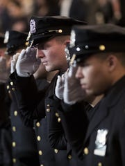 New members of the New York City Police Department salute during their police academy graduation ceremony.
