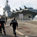 Navy soldiers walk to France's nuclear-powered aircraft carrier Charles de Gaulle at its home port of Toulon, southern France, Wednesday, Nov.18. France has decided to deploy its aircraft carrier in the eastern Mediterranean sea for fighting Islamic State group.