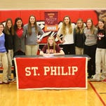 St. Philip senior Abby McKinzie (center) has signed a National Letter of Intent to play volleyball at Virginia Tech. She is surrounded by members of the St. Philip volleyball team.