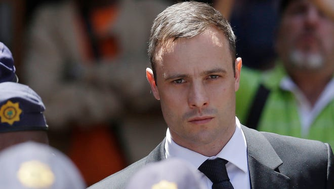 Oscar Pistorius is escorted by police officers as he leaves the high court in Pretoria, South Africa, earlier this year.