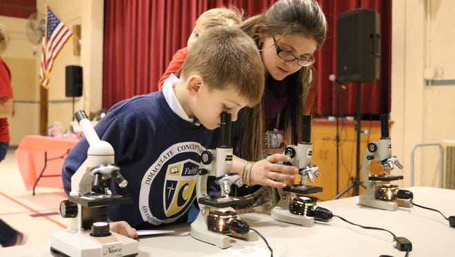 Clark Fry, 6, peeks into a microscope during Science Night at Immaculate Conception School.