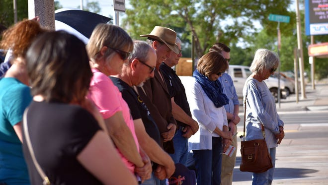 Community members pray Thursday during the National Day of Prayer event on the steps of the Otero County Courthouse.