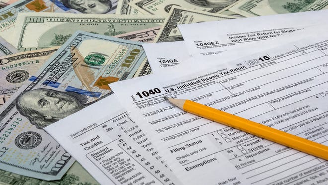Tax forms on top of money.