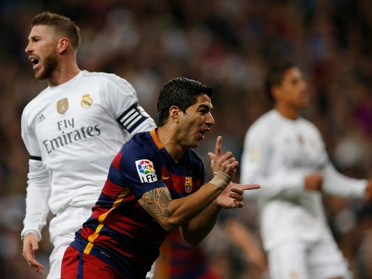 FILE - In this Nov. 21, 2015 file photo, Barcelona's Luis Suarez celebrates after scoring the opening goal during the first clasico of the season between Real Madrid and Barcelona at the Santiago Bernabeu stadium in Madrid, Spain. The rivalry between Real Madrid and Barcelona is heating up before a match in which Madrid isn't even playing. Barcelona will face Sevilla in the Copa del Rey final in May, but the discussion in Spain is about whether Real Madrid will allow the game to be played at its Santiago Bernabeu Stadium or force officials to choose a different venue. Most Real Madrid fans wouldn't want to see Barcelona winning a title at their stadium again. It happened in 1997, when Barcelona won the Copa del Rey title over Real Betis. Barcelona supporters filled the Bernabeu wearing their team's colors, and players lifted the trophy with the club's hymn being played loudly through the stadium's speakers. (AP Photo/Daniel Ochoa de Olza, File)