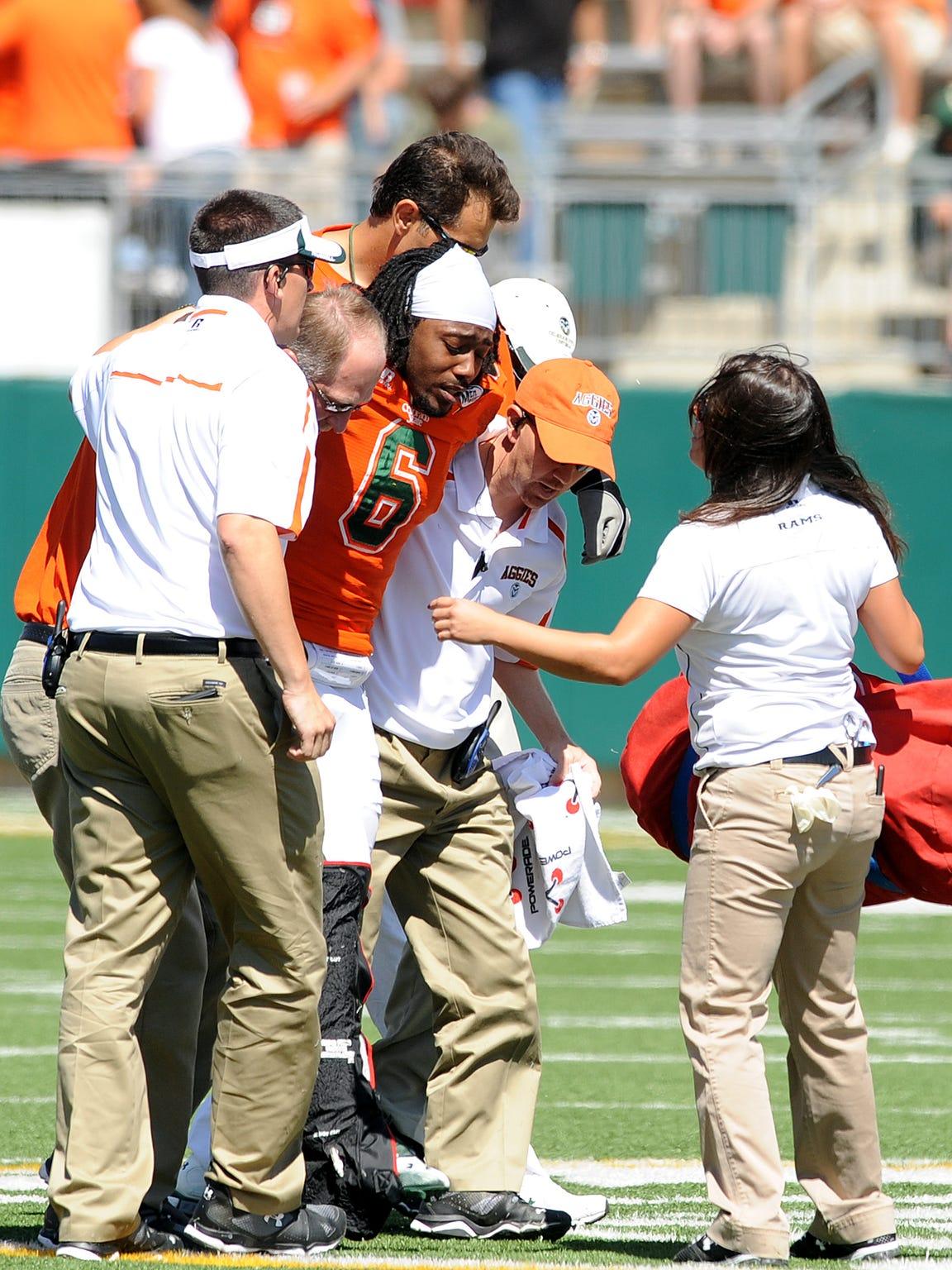CSU linebacker Myke Sisson is helped off the field