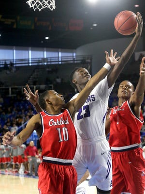 Southwind's Kameron Jones (23) grabs a rebound between Oakland's Michael Hayworth (10) and Tre Jones (1) during the quarterfinal round of the Class AAA State Tournament on Wednesday, March 15, 2017.