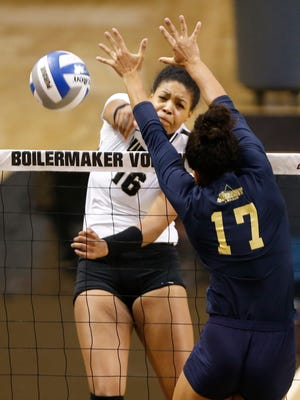 Purdue's Sherridan Atkinson with a spike over CeCe Madison of Oral Roberts Friday, August 25, 2017, at Holloway Gymnasium on the campus of Purdue University. Purdue defeated Oral Roberts 25-15, 25-13, 25-20.