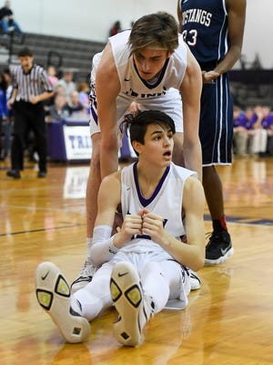 TCA's Vann Bryant helps his teammate Clark Larson after he was fouled during their game against Madison Academic, Thursday, Feb. 15. TCA defeated Madison, 57-53.