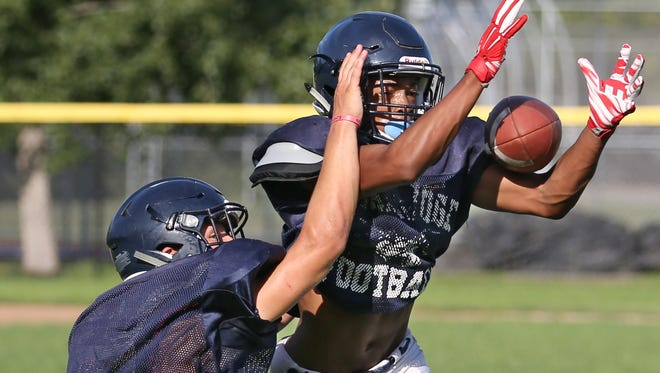 Eastridge defensive back Jake Trynoski, left, dives to knock the ball away from Jadon Turner during coverage drills during their practice at Eastridge High School in Irondequoit Wednesday, Aug. 24, 2016.