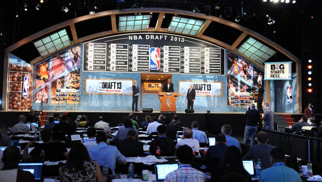 NBA commissioner David Stern, deputy commissioner Adam Silver and former NBA player Hakeem Olajuwon speak on stage after the first round of the 2013 NBA Draft.
