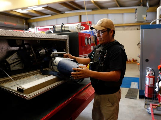 Firefighter Derrick Woody shows some of the extraction tools stored in their department's brush truck on Thursday at San Juan County District 12 Fire Department in Shiprock.