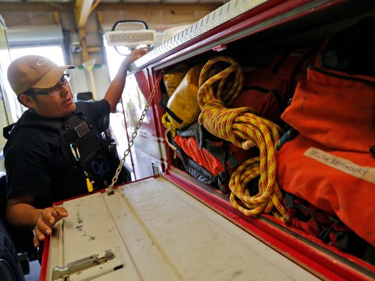 Firefighter Derrick Woody talks about the various high angle rescue gear that is stored in their brush truck on Thursday at the San Juan County District 12 Fire Department in Shiprock.