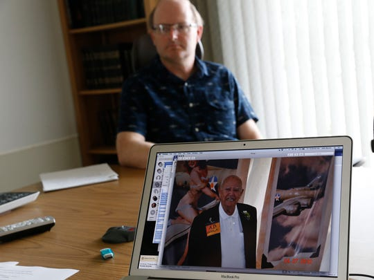 D.J. Simmons Finance Officer Jeff Parkes and outgoing CEO John Byrom, not pictured, look over photos of A.B. Geren on July 1 at the offices of  D.J. Simmons in Farmington.