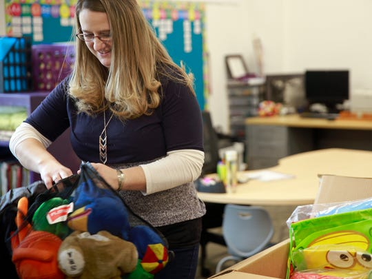 Kindergarten teacher Kali Warner unpacks a box in her classroom on Monday at the new Judy Nelson Elementary School in Kirtland. Teachers used the winter break to organize classrooms.
