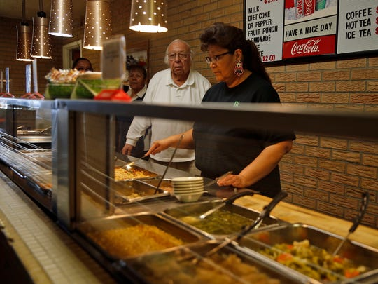 Bernie Sandoval, owner and manager of Chef Bernie's Restaurant, and Drusilla Begay prepare food in the buffet line at Chef Bernie's Restaurant on Monday.
