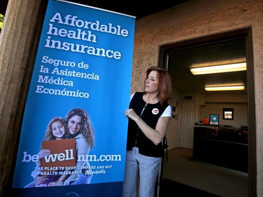 Enrollment counselor Ginger Lewis moves a banner outside the New Mexico Health Insurance Exchange's Farmington Enrollment and Assistance Center.