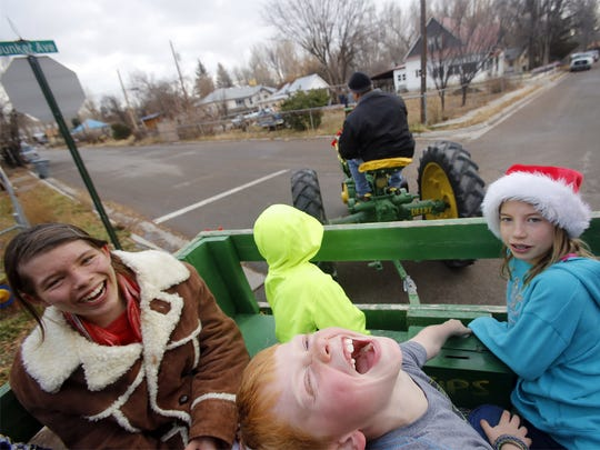 Crystal Tradup, left, Justice Farrell, Dalton Eaton and Kamry Johnson enjoy a tractor ride provided by the Four Corners Antique Power Association's Greg Tradup Saturday during the second annual Aztec Sparkles event. Crystal Tradup, left, Justice Farrell, Dalton Eaton and Kamry Johnson enjoy a tractor ride provided by the Four Corners Antique Power Association's Greg Tradup Saturday during the second annual Aztec Sparkles event.