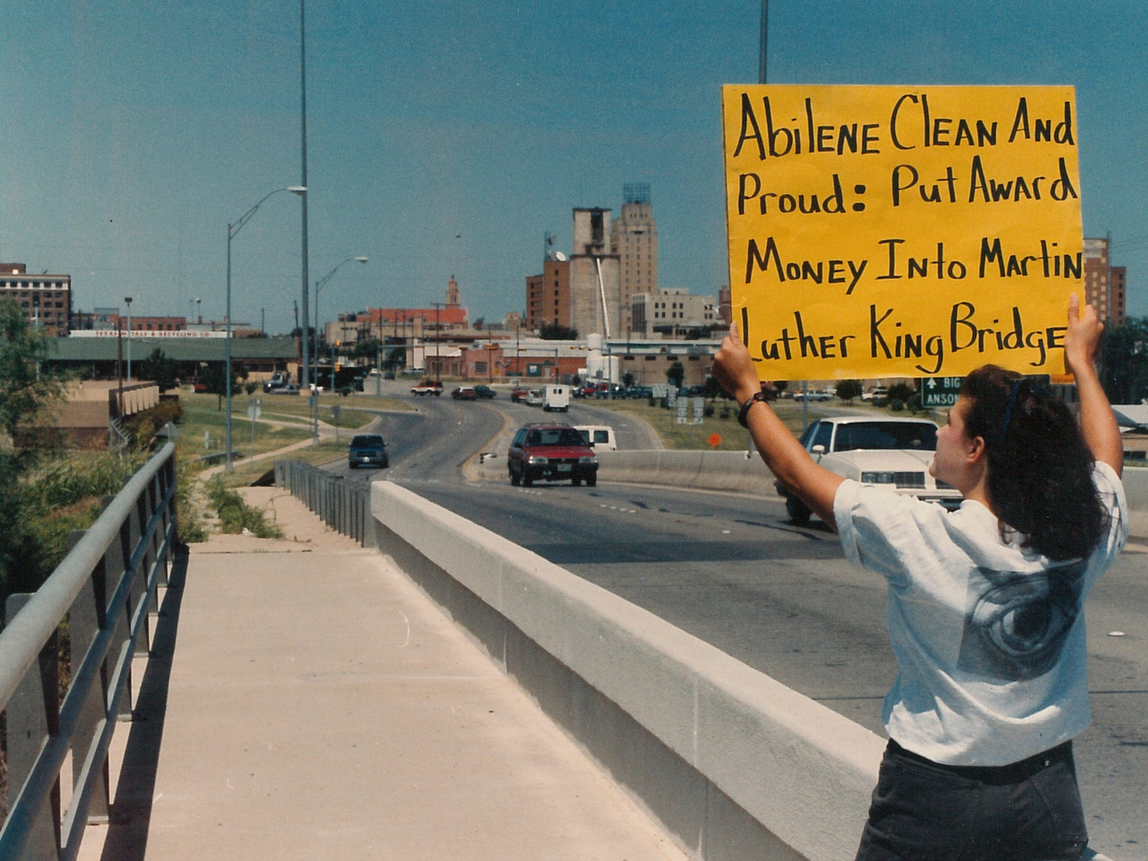 A woman holds a sign in July 1992 hoping to inspire dressing up an east Abilene bridge to honor the late Martin Luther King Jr. In 1993, the bridge was renamed in King's honor and more than $100,000 was spent to plant trees and erect a marker at the west end.