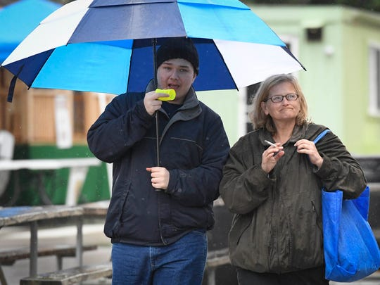 James and Betty Weis share a umbrella as they see what's available at the Henderson Breakfast Lions Club Tri-Fest Saturday, April 22, 2017.