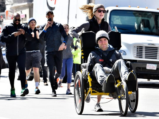 Kaitlyn Kiely pushes her longtime boyfriend, Matt Wetherbee, as they approach the Boston Marathon finish line on Monday, April 9. Friends and family run with the couple providing motivation and support.