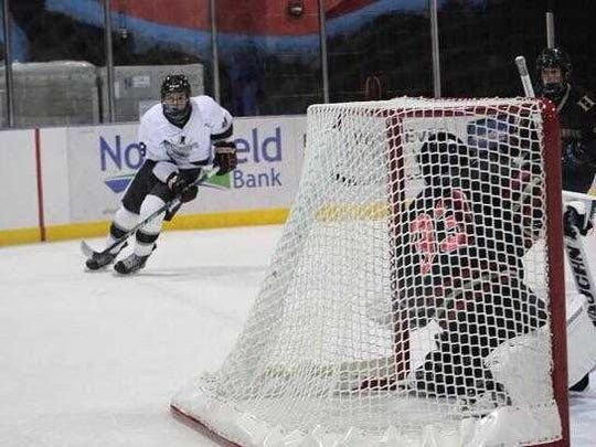 Drew Galea (white jersey) skates toward the net in a recent Colonia ice hockey game.