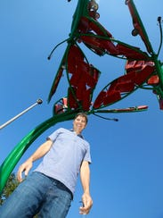 Sculptor Christopher Fennell stands next to his latest