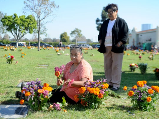 Guadalupe Ambriz and her aunt, Ester Ambriz (standing), bring flowers to Guadalupe's father, Antonio Ambriz, during a past Dia de los Muertos event at Santa Clara Cemetery. This year's event will be Oct. 28.
