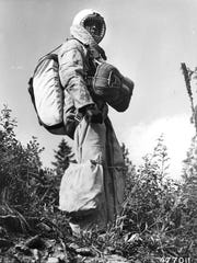 Bill Carver, foreman in smokejumper unit at Missoula, is suited up in a complete smokejumper's outfit in 1954.